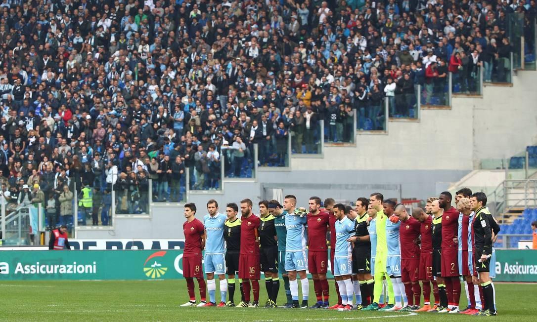 Jogadores de Lazio e Roma se abraçaram no centro do campo do Estádio Olímpico de Roma e fizeram um minuto de silêncio em sentimento às vítimas do voo da Chapecoense, antes do início do clássico entre as equipes Foto: ALESSANDRO BIANCHI / REUTERS