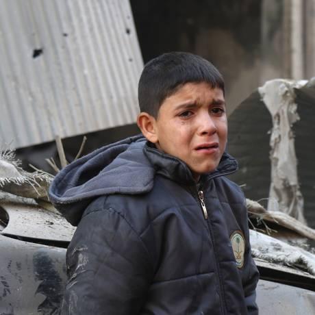 Menino chora ao lado de prédio destruído por ataques aéreos em vilarejo de Idlib, na Síria Foto: MOHAMED AL-BAKOUR / AFP