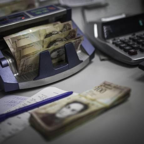 Máquina de contar dinheiro em escritório de padaria em Caracas Foto: Wil Riera / Bloomberg