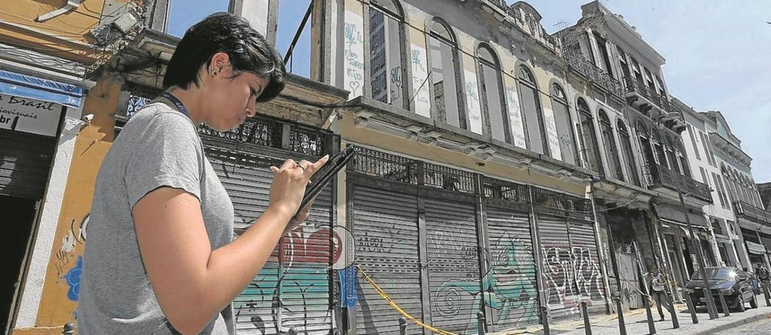 Pesquisadora usa tablet para registrar imóveis em rua do Centro: expectativa é mapear 4.700 endereços em três meses Foto: Domingos Peixoto / Agência O Globo
