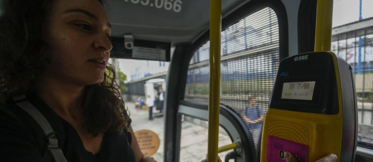 Passageira paga o valor integral da tarifa de ônibus intermunicipal em Niterói Foto: Gabriel de Paiva / O Globo