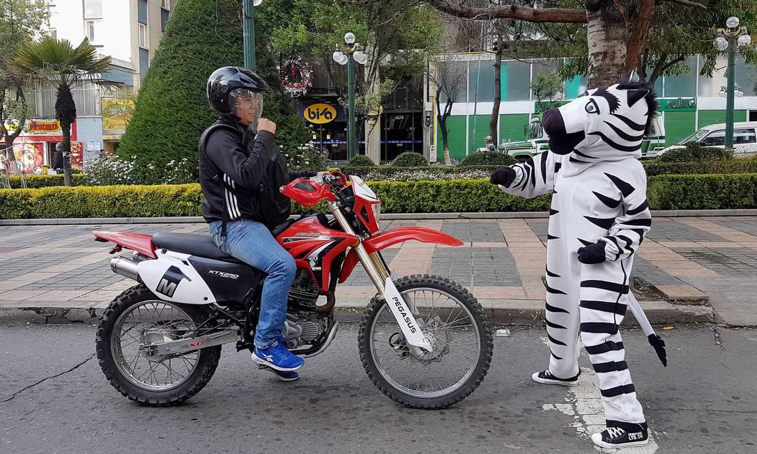 Moradores, vestidos de zebra, conversam com motoristas como parte do programa de educação de estrada em La Paz, Bolívia DAVID MERCADO / REUTERS