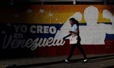 """Mulher caminha por muro que diz """"eu acredito na Venezuela"""" em Caracas Foto: UESLEI MARCELINO / REUTERS"""