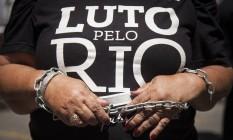 Manifestante com camisa que fala de luto pelo Rio usa correntes em protesto na porta lateral da Alerj Foto: Hermes de Paula / O Globo