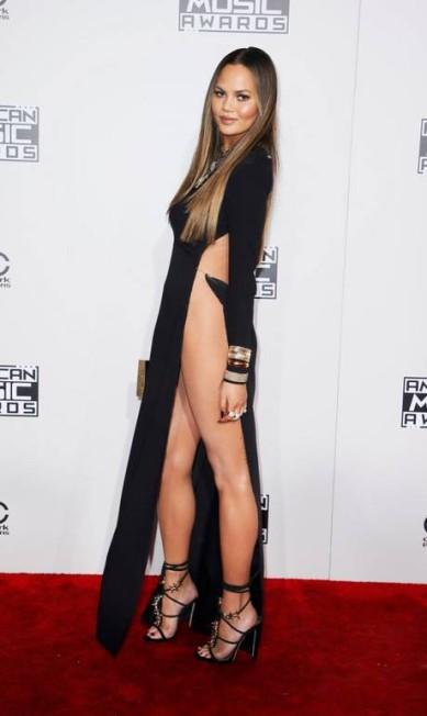 Haja perna para tanta fenda! A modelo Chrissy Teigen parou tudo na noite do último domingo ao desfilar pelo tapete vermelho do American Music Wards com um vestido que deixava muito pouco para a imaginação DANNY MOLOSHOK / REUTERS