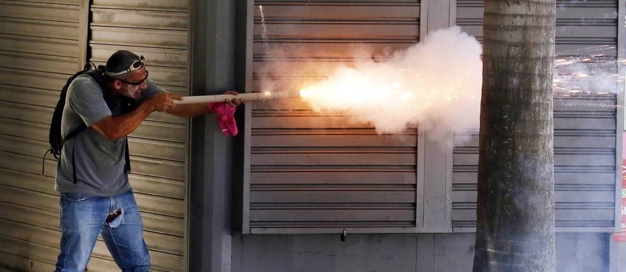Homem usando leite de magnésia no rosto atira morteiro contra os policiais Foto: Pablo Jacob / Agência O Globo