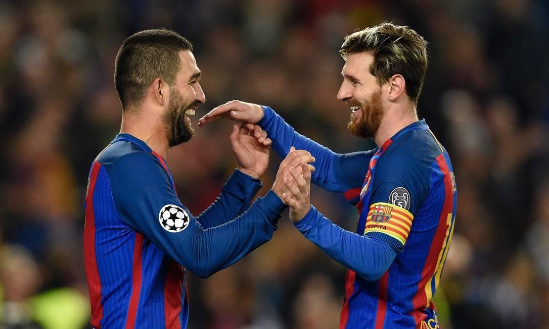 Arda Turan, à esquerda, abraça Messi ao fazer um de seus três gols sobre o Borussia LLUIS GENE / AFP