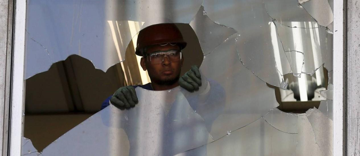 Homem retira vidro quebrado no prédio do Banerjão Foto: Pablo Jacob / Agência O Globo
