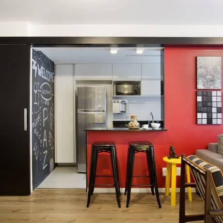 Na cozinha aberta a parede pintada com tinta comum, à óleo, serve como lousa para recados e receitas Foto: MCA Studio / Divulgação