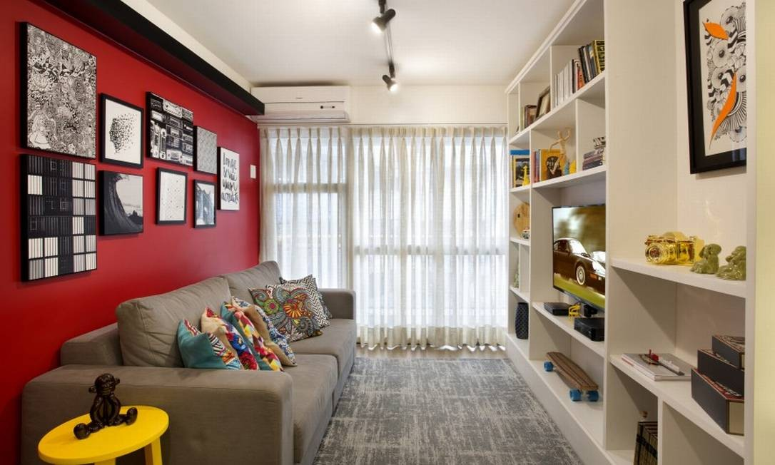 A parede cor de cereja era o desejo principal da moradora e colore o living Foto: MCA Studio / Divulgação