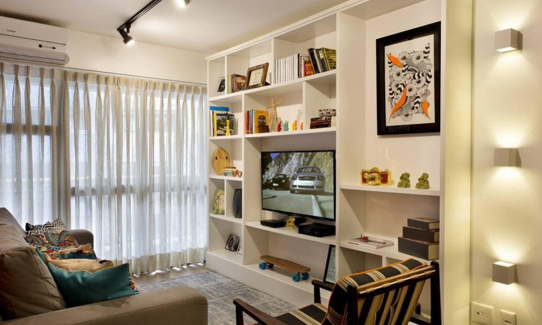 A arquiteta desenhou toda a marcenaria da casa, como essa estante, pintada de branco. A iluminação também foi estudada para dar mais personalidade ao ambiente Foto: MCA Studio / Divulgação