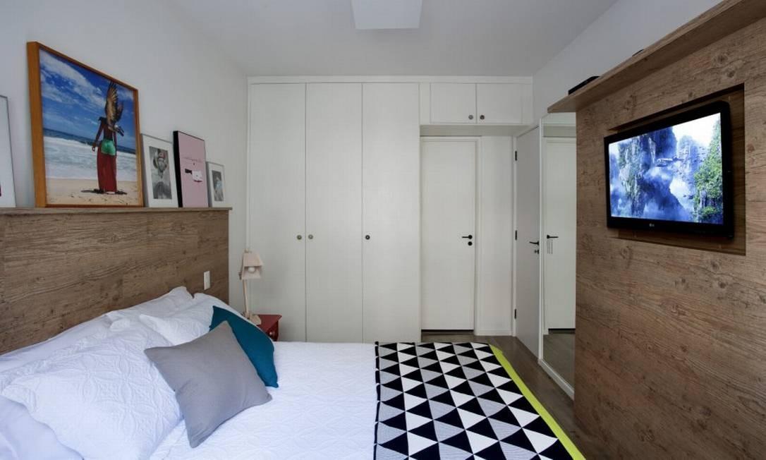 No quarto, painéis de marcenaria servem como cabeceiras de cama com apoio para quadros e em frente, para abrigar a televisão Foto: MCA Studio / Divulgação