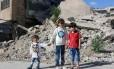 Infância no front. Bana al-Abed (centro), com os irmãos, em meio a escombros em Aleppo Foto: THAER MOHAMMED / AFP