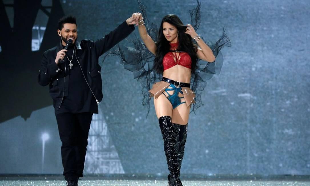 Uma semana antes, Adriana Lima dominou o desfile da Victoria´s Secret em Paris. Aqui, ela monopoliza a atenção do cantor The Weeknd CHARLES PLATIAU / REUTERS