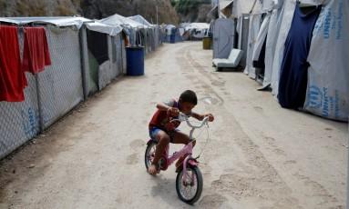Menino anda de bicicleta em campo de refugiados na ilha grega de Chios Foto: Alkis Konstantinidis / REUTERS