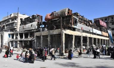 Sírios fogem de bairros rebeldes de Aleppo com seus pertences Foto: SANA / REUTERS