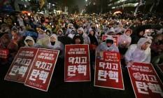 Pelo afastamento da presidente. Mesmo debaixo de chuva, milhares de manifestantes tomam as ruas de Seul, próximo ao Parlamento, para pedir a saída de Park Geun-hye Foto: Ahn Young-joon/AP