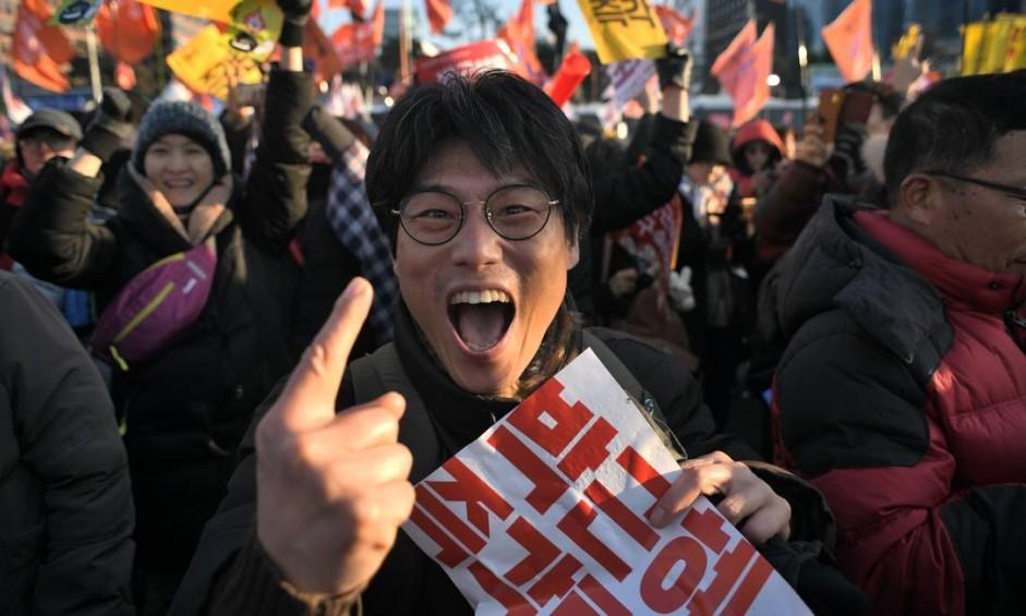 Manifestante comemora a aprovação do impeachment da presidente Park Geun-hye, acusada de conspiração para tráfico de influência Foto: ED JONES / AFP