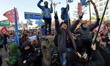 Multidão comemora impeachment contra Park Geun-hye em frente à Assembleia Nacional em Seul. No cartaz, os dizeres 'Prendam Park Geun-hye' Foto: STRINGER / REUTERS