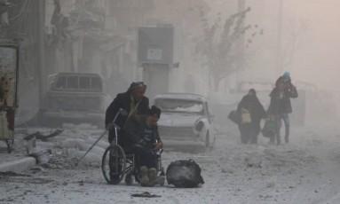 Homem em cadeira de rodas é transportado às pressas para fugir de área bombardeada em Aleppo Foto: ABDALRHMAN ISMAIL / REUTERS
