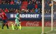 O goleiro do Osasuna apenas observa Messi marcar o segundo gol do Barcelona em Pamplona Foto: CESAR MANSO / AFP