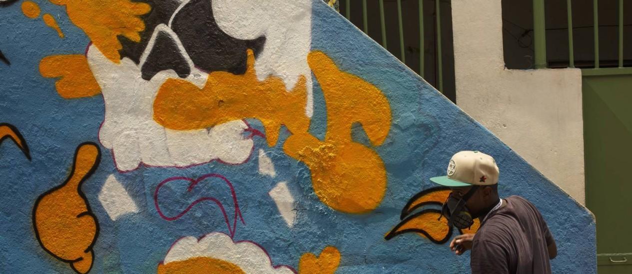 Grafiteiro desenha num paredão: arte é renovada todo ano Foto: Daniel Marenco / O Globo