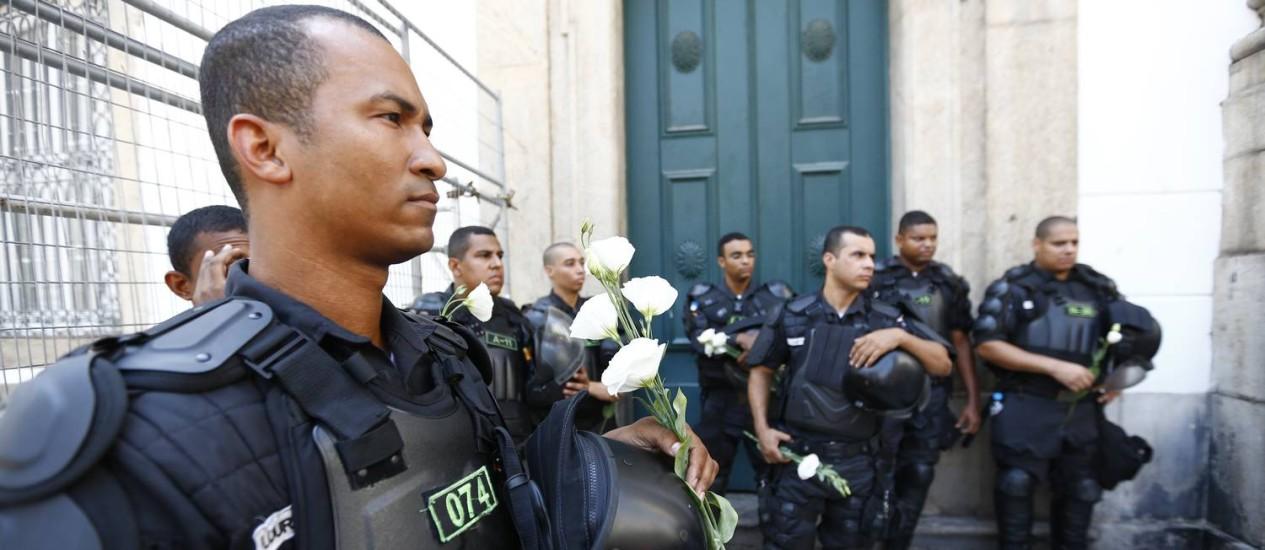 Policiais militares seguram rosas brancas que foram distribuídas por manifestantes Foto: Pablo Jacob / O Globo