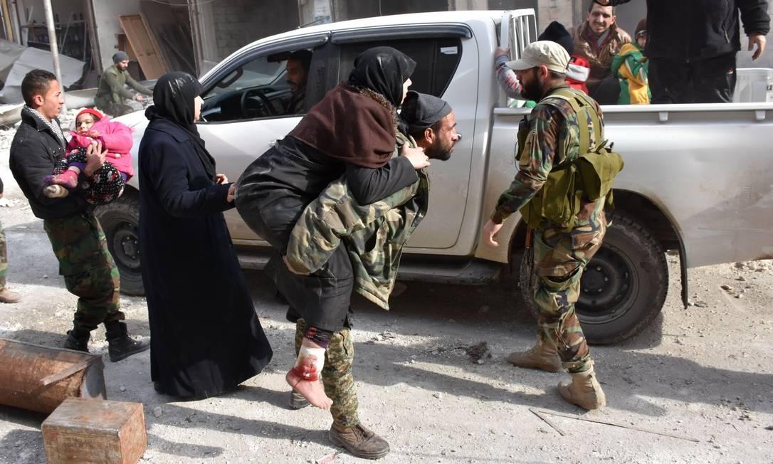Combatente pró-governo carrega nos braços uma mulher que foi ferida enquanto tentava fugir com a sua família dos combates em Aleppo Foto: GEORGE OURFALIAN / AFP