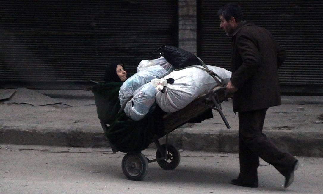 Sírios fogem com seus pertences dos combates em Aleppo; batalha entre insurgentes e governo está em fase final após avanços em série do governo pelo território Foto: STRINGER / AFP