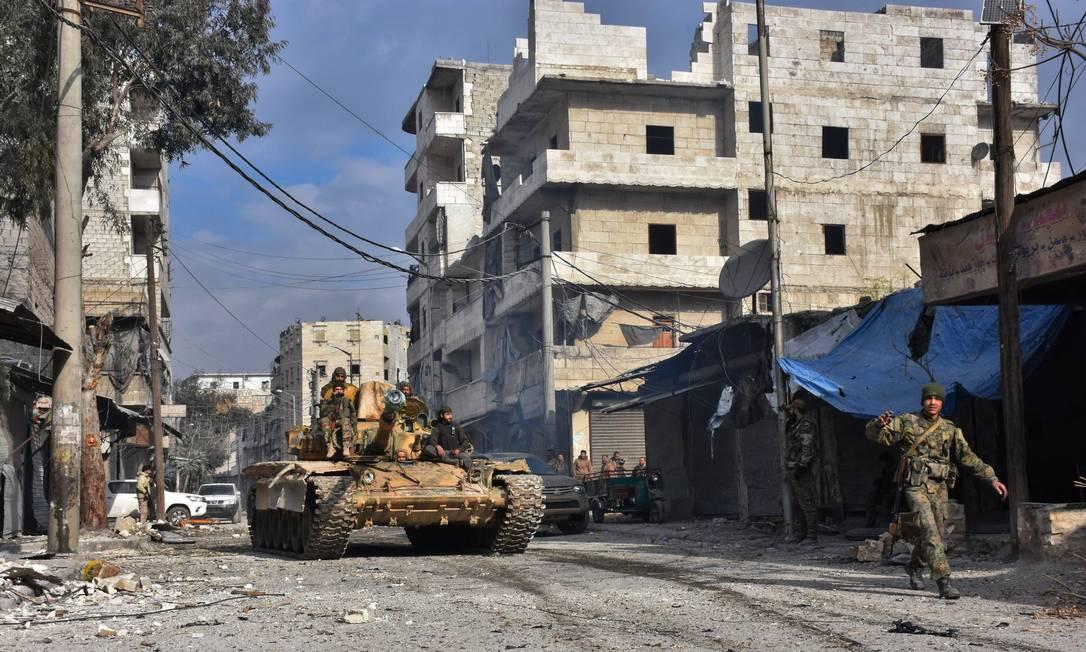 Soldados sírios fazem patrulha em bairro que era controlado por insurgentes; ofensiva do governo provocou fuga em massa de civis Foto: GEORGE OURFALIAN / AFP