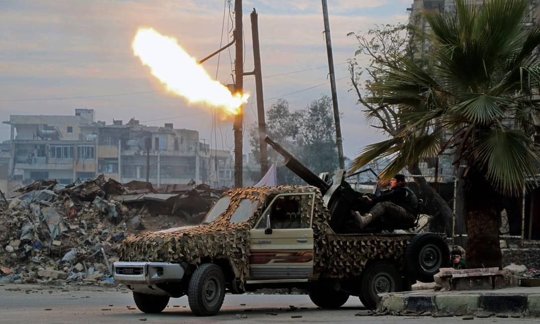 Combatentes do Exército Livre da Síria disparam arma contra aviões militares no bairro de Mashhad, em Aleppo Foto: STRINGER / AFP