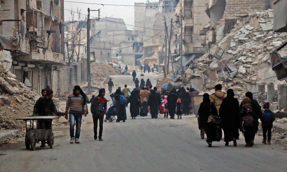 Sírios deixam suas casas em bairro controlado por rebeldes durante operação do regime para retomar áreas insurgentes em Aleppo Foto: STRINGER / AFP