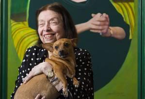 Nélida em seu apartamento, com a cachorra Suzy e um retrato pintado por Glauco Rodrigues: memória cobre as paredes da casa, com quadros, diplomas, títulos e homenagens Foto: Leo Martins