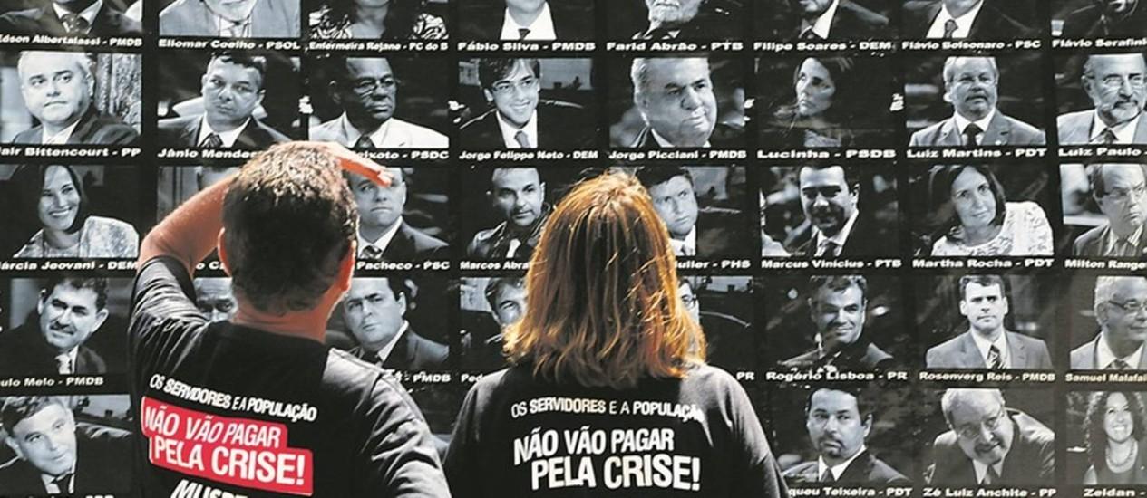 Manifestantes observam um painel com retratos de deputados colocado do lado de fora da Alerj: representantes dos servidores também vão ser chamados para opinar sobre o pacote anticrise do estado Foto: Gabriel de Paiva / O Globo