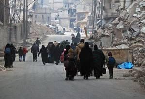 Civis sírios fogem do bairro de Sukkari em direção a áreas mais seguras de rebeldes no sudeste de Aleppo Foto: STRINGER / AFP