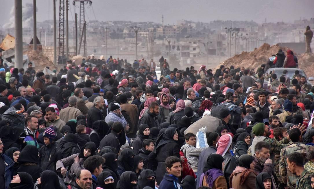 Famílias sírias fogem de vários distritos de Aleppo e fazem fila para entrar nos ônibus do governos, em Jabal Badro, no dia 29 de novembro. A ofensiva governamental para recuperar a cidade acendeu um alerta internacional; a ONU informou que cerca de 16 mil pessoas fugiram do ataque e que mais poderiam seguir o mesmo caminho. A guerra criou um êxodo de civis aterrorizados, fugindo de mãos vazias para os poucos territórios rebeldes restantes Foto: George Ourfalian / AFP