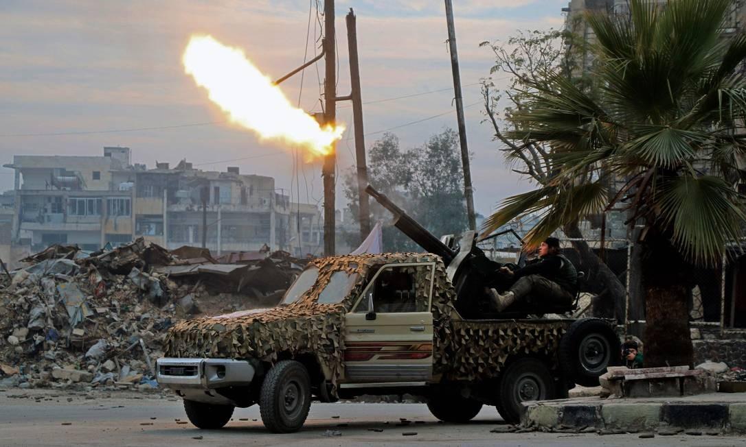 Soldados do Exército Livre da Síria disparam ao sudeste de Aleppo, em 12 de dezembro, no combate às forças governistas. A guerra de Aleppo entra em sua fase final depois de bombardeios forçarem a retirada dos rebeldes Foto: Stringer / AFP