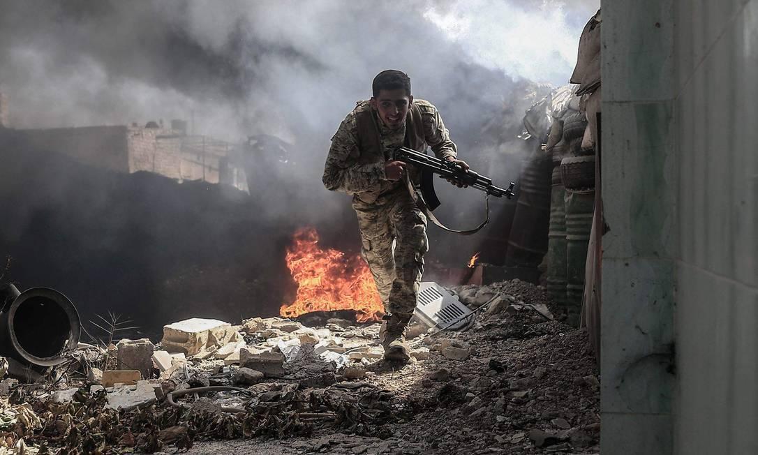 Combatente do grupo Jaish al-Islam foge de tiros, na aldeia de Tal al-Siwan, área controlada pelos rebeldes, nos arredores de Damasco, no dia 5 de setembro Foto: SAMEER AL-DOUMY / AFP