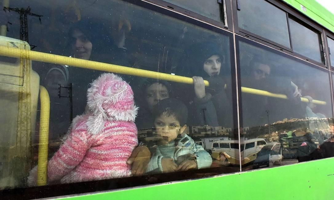 Famílias sírias fogem de vários pontos da cidade de Aleppo, em um ônibus no dia 29 de novembro Foto: George Ourfalian / AFP