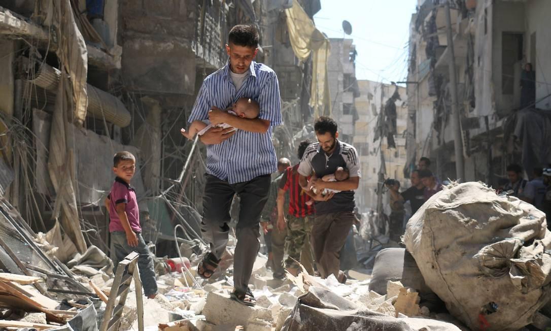 Sírios carregam bebês em meio aos destroços depois de um ataque aéreo no bairro rebelde de Salihin, ao norte da cidade de Aleppo, no dia 11 de setembro. Bombardeios já mataram dezenas em áreas rebeldes Foto: Ameer Alhalbi / AFP