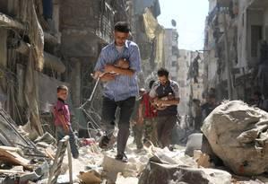 Homens sírios carregam bebês nos destroços depois de um ataque aéreo no bairro rebelde de Salihin, ao norte da cidade de Aleppo, no dia 11 de setembro. Bombardeios já mataram dezenas em áreas rebeldes, enquanto a oposição considera se se une à trégua russa ou não Foto: AMEER ALHALBI / AFP