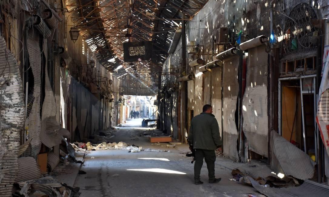 Soldado sírio anda por comércio fechado no distrito da Cidade Antiga de Aleppo Foto: George Ourfalian / AFP