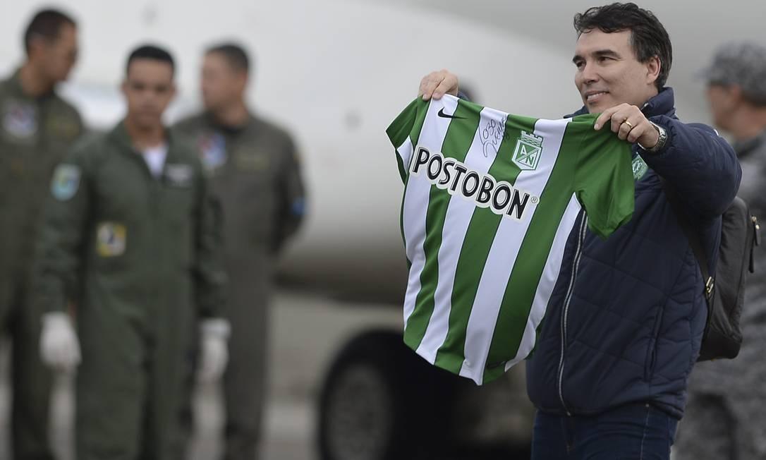 O médico Carlos Mendonça exibe a camisa do Atlético Nacional de Medellín antes de embarcar no avião que levaria os sobreviventes Alan Ruschel e Rafael Henzel de volta a Chapecó RAUL ARBOLEDA / AFP