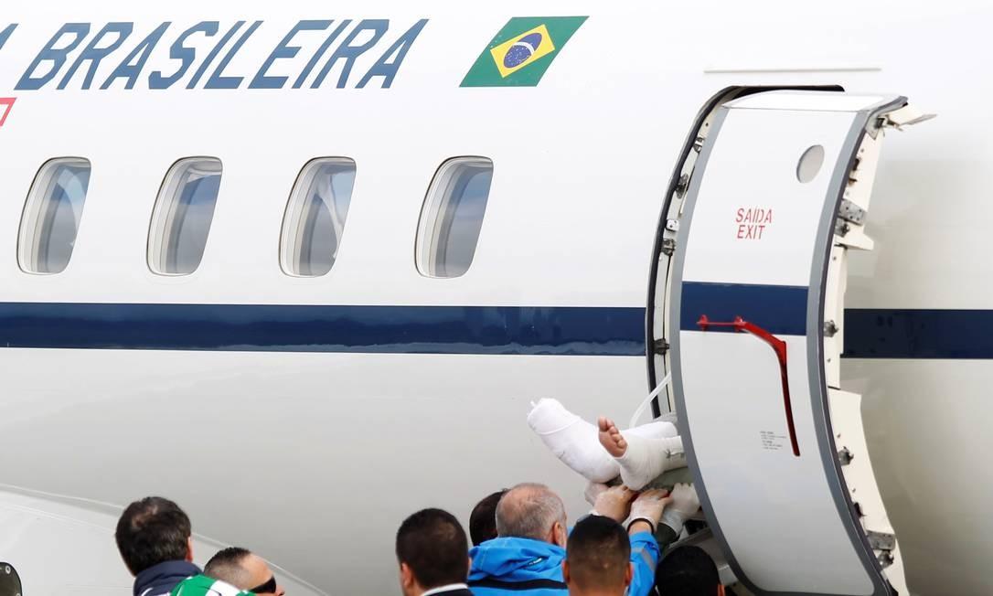 As pernas engessadas de Rafael Henzel aparecem no momento em que a maca com o jornalista, sobrevivente do voo da Chapecoense, é colocada no avião da FAB no regresso dele e do lateral Alan Ruschel a Chapecó FREDY BUILES / REUTERS
