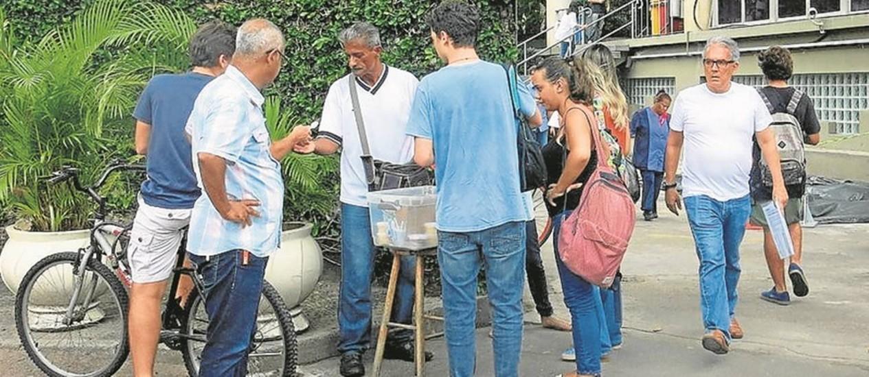 Dinheiro extra. Haroldo e os clientes: ele vende bolos há três meses e meio na porta da PUC Foto: Isabella Cardoso