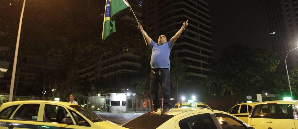 Taxista sobe em veículo durante protesto Foto: Pedro Teixeira / Agência O Globo