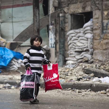 Menino sírio carrega sacolas com pertences enquanto civis deixam áreas rebeldes de Aleppo Foto: KARAM AL-MASRI / AFP