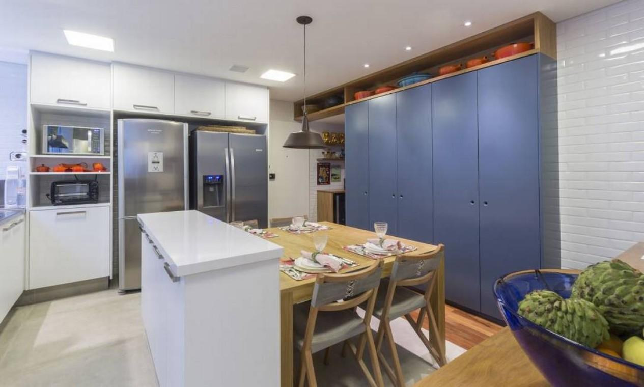 Aqui, o azul do armário e o laranja de vários utensílios ornam com o branco da bancada e outras estruturas. Projeto da arquiteta Julyana Bortolotto Foto: Divulgação