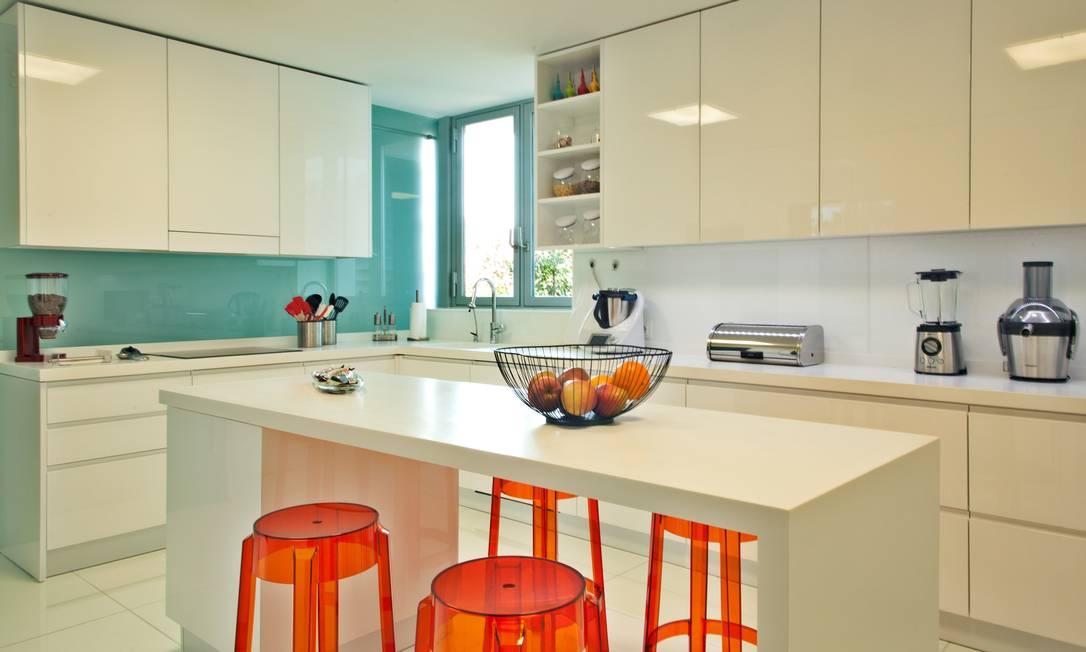 A arquiteta Andrea Chicharo deu vida à cozinha predominantemente branca com uma parede verde-água e bancos laranjas Divulgação