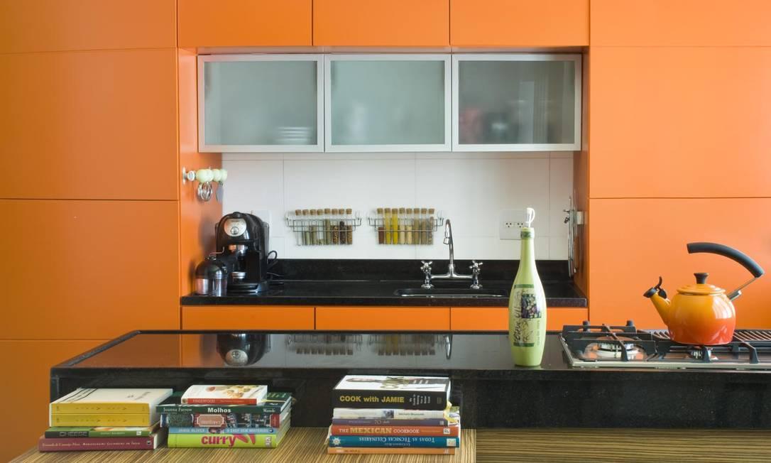Os armários modulados em tom de tangerina fazem oposição ao preto dos mármores. Projeto da Escala Arquitetura Foto: Divulgação / izfotos